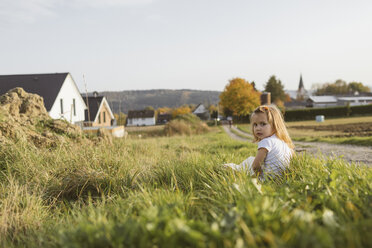 Portrait of blond little girl sitting on a meadow with a book - KMKF00073