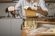 Woman preparing homemade pasta, using pasta maker - MAUF01260