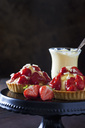 Two strawberry tartlets with custard and white chocolate shaving on cake stand - CSF28582