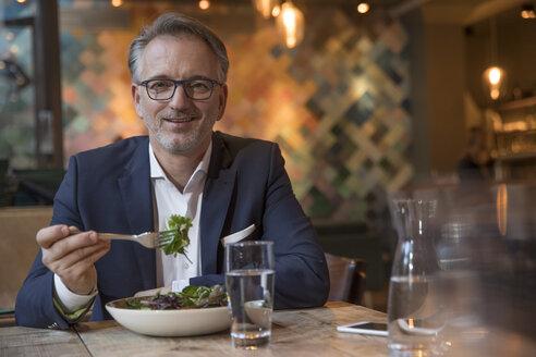 Portrait of businessman having lunch in a restaurant - SUF00348