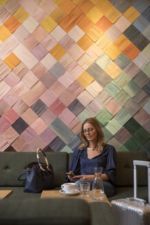 Portrait of businesswoman with baggage in a cafe looking at cell phone - SUF00360