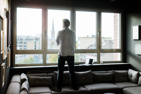 Businessman in lounge area of an office looking out of window - JOSF02014