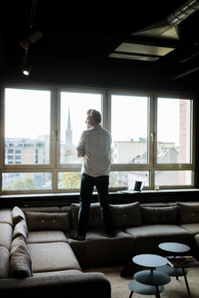 Businessman in lounge area of an office looking out of window - JOSF02020