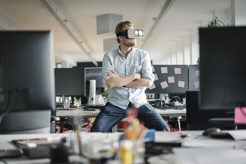 Businessman wearing VR glasses in office - JOSF02029