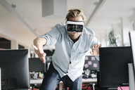 Businessman wearing VR glasses in office - JOSF02032