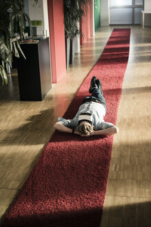 Businessman lying on carpet on the floor in office wearing VR glasses - JOSF02035