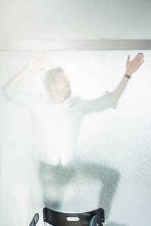 Businessman trapped behind glass pane in office - JOSF02038