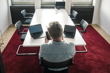Businessman in conference room of an office with two laptops - JOSF02041