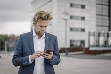 Businessman using cell phone in the city - JOSF02053