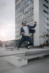 Businessman wearing VR glasses jumping in the city - JOSF02059