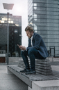 Businessman sitting on bench in the city using cell phone - JOSF02071