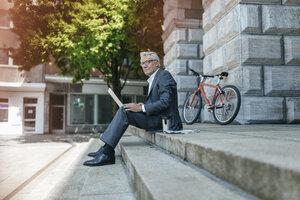Senior businessman sitting on stairs, using laptop - GUSF00256