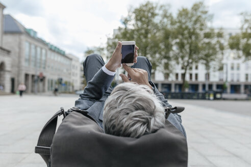 Senior businessman using smartphone, lying on bench in the city - GUSF00262