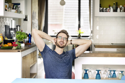 Portrait of smiling young man sitting at kitchen table at home - PESF00753