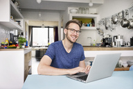 Portrait of smiling man using laptop in kitchen at home - PESF00759