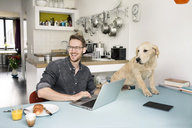 Portrait of happy man with dog using laptop in kitchen at home - PESF00762
