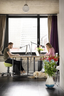 Man and woman with dog working at desk at home - PESF00768