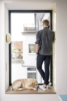 Man on the phone standing at the window next to dog - PESF00771
