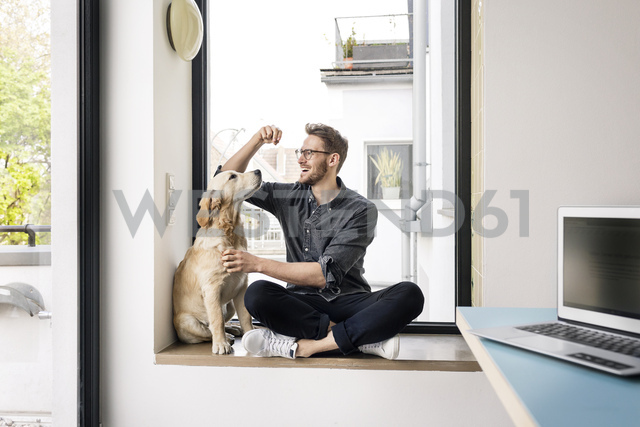Happy man with dog sitting at the window - PESF00777 - Peter Scholl/Westend61