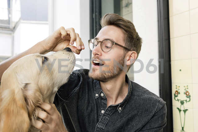Young man feeding dog at the window - PESF00780