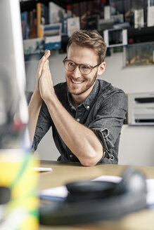 Portrait of smiling man working at desk at home - PESF00786