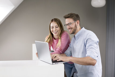 Happy man and woman sharing laptop - PESF00795