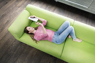 Young woman lying on the couch using tablet - PESF00798