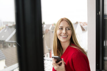 Smiling young woman at the window in city apartment holding cell phone - PESF00807