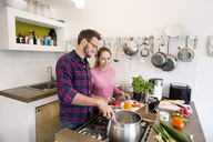 Happy young couple with tablet cooking together in kitchen - PESF00816