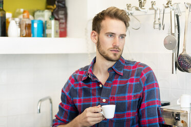 Pensive young man with cup of espresso in kitchen at home - PESF00819
