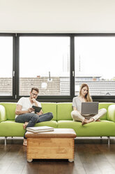 Young couple in living room at home using laptop and tablet - PESF00831