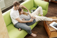 Young couple on couch in living room at home sharing tablet - PESF00834