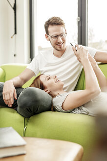 Smiling young couple on couch in living room at home sharing cell phone - PESF00837