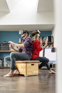 Young couple at home sitting on box wearing VR glasses - PESF00840