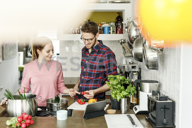 Happy young couple with tablet cooking together in kitchen - PESF00843