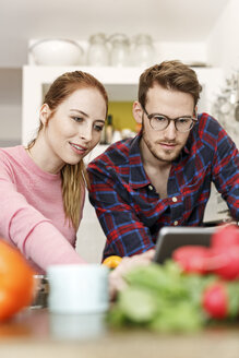 Young couple using tablet cooking together in kitchen - PESF00846