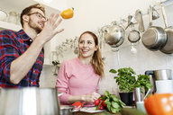 Happy young couple cooking together in kitchen - PESF00849