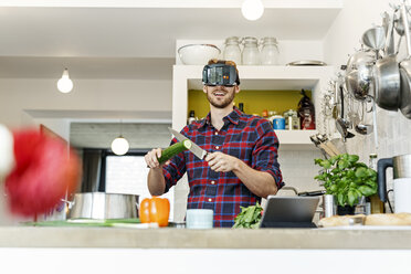 Happy young man wearing VR glasses cooking in kitchen - PESF00852