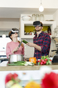 Happy young couple wearing VR glasses cooking together in kitchen - PESF00855