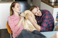 Happy young couple cuddling with dog at home - PESF00861