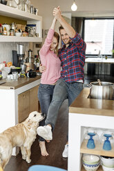 Young couple with dog dancing in the kitchen - PESF00864