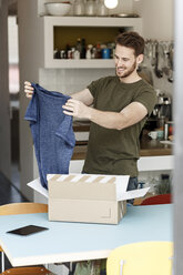Smiling young man at home unpacking parcel with clothing - PESF00867