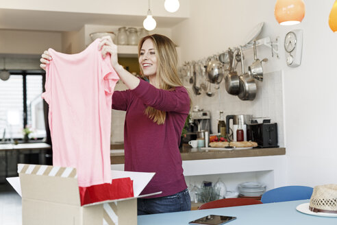 Smiling young woman at home unpacking parcel with clothing - PESF00870