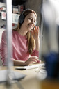 Smiling young woman wearing headphones at desk at home - PESF00873