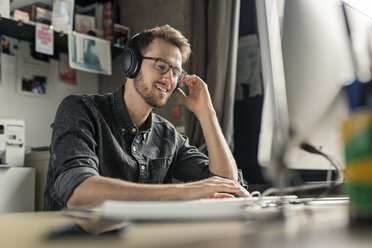 Smiling young man wearing headphones working on computer at desk at home - PESF00885