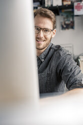Portrait of smiling young man behind computer screen at desk at home - PESF00888