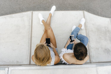Two young women using cell phones in a skatepark - KNSF03054