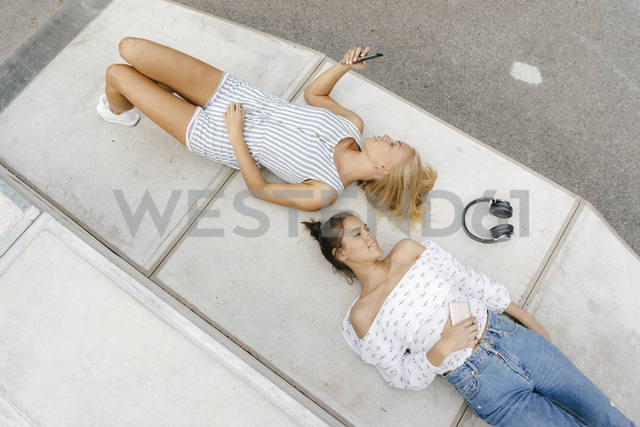 Two young women with cell phone and headphones in a skatepark - KNSF03063