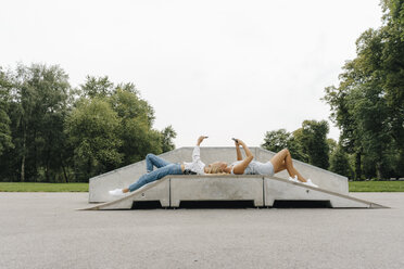 Two young women with cell phones lying on ramp in a skatepark - KNSF03066