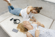 Two happy young women lying on ramp in a skatepark making music - KNSF03069